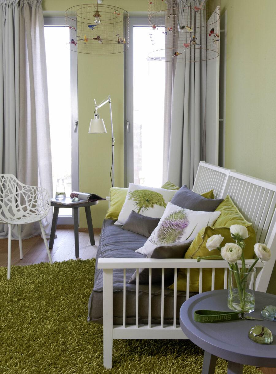 """Gemütlich in der Gartensuite des LÖSCH für Freunde: das Sofa """"Gray"""" der Marke Gervasoni. Darüber zwitschern bunte Ziervögel in den filigranen Lampen, entworfen vom Designer Mathieu Challières"""